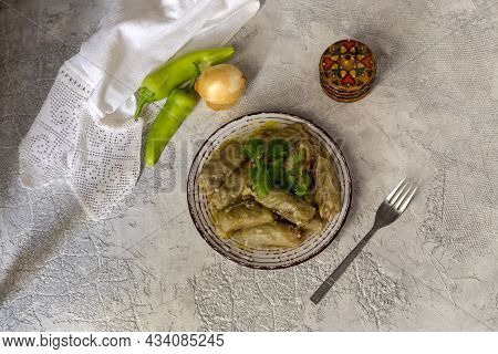 Portion Of Stewed Cabbage Rolls In Egg-lemon Sauce (lahanodolmades) On A Wooden Table Close-up (gree