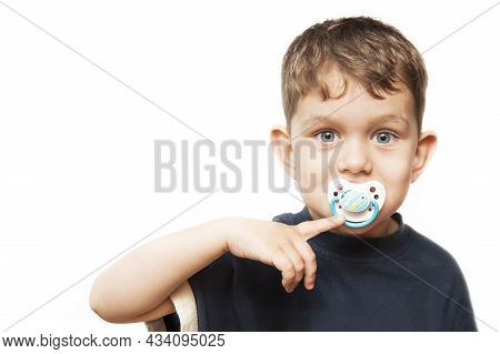 Portrait Of A Young Boy On A White Background With A Dummy - Baby Pacifier In His Mouth. He Smiles B