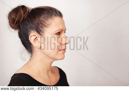 Portrait Of A Sad Woman In A Profile On A Gray Background. She Looks To The Side And Gets Sad Becaus