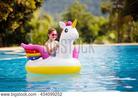 Child On Unicorn Float In Swimming Pool Of Tropical Resort. Kids Swim And Play With Inflatable Water