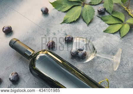 Bottle Of Red Wine, Green Vine, Wineglass And Ripe Grape On Vintage Dark Stone Table Background. Top