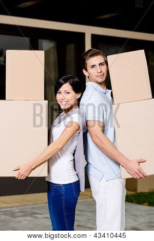 Happy couple stands back to back while carrying cardboard boxes and moving to new house