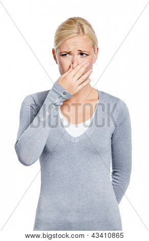 Female covers nose with hand showing that something stinks, isolated on white