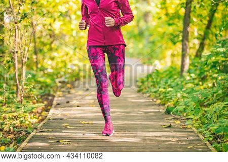 Run in forest at fall. Fit woman running in nature outdoors doing fitness workout in autumn park. Girl athlete jogging outdoor.