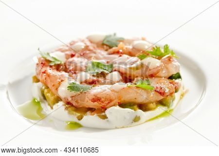 Restaurant dish - shrimp tartare with avocado, cream cheese, sweet chilli sauce on white plate. Ceviche with marinated prawn, avocado and spicy vegetables. Prawn tartare isolated on white background