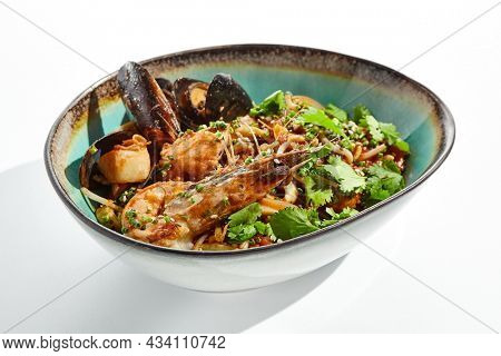 Japanese soba with seafood cooked on wok in asian style on white background. Noodle seafood in ceramic bowl. Indonesian wok with prawn, mussels and soba noodles. Spicy thai dish with shrimp and udon