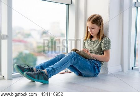 Preteen girl sitting on windowsill and reading paper book with daylight. Beautiful kid schoolgirl learning doing homework at home