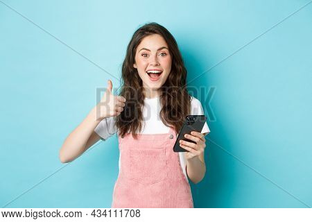 Portrait Of Excited Cute Girl Say Yes, Smiling And Nod In Approval, Holding Smartphone While Showing
