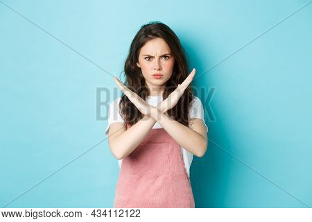 Image Of Young Disappointed Woman Frowning, Making Cross Sign And Sulking, Showing Stop Gesture, Say