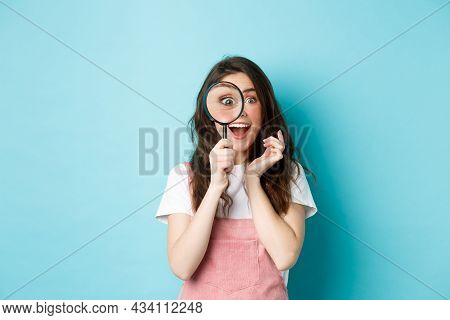 Happy Young Woman Looking Through Magnifying Glass With Excited Face, Found Or Search Something, Sta