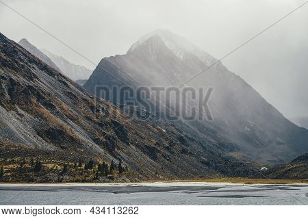 Gloomy Autumn Foggy View To Gray Mountain Lake And Rocky Pinnacle With Snow On Top In Haze In Rainy