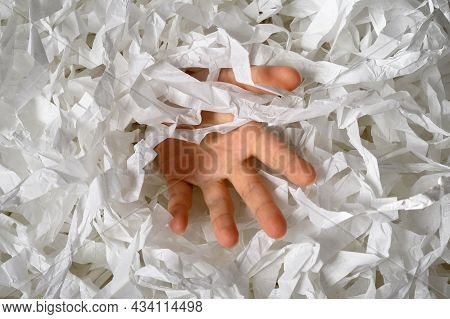 Hand Reaches Out From Heap Of Shredded Paper, Man Sinking In Pile Of White Confetti. Somebody Drowni