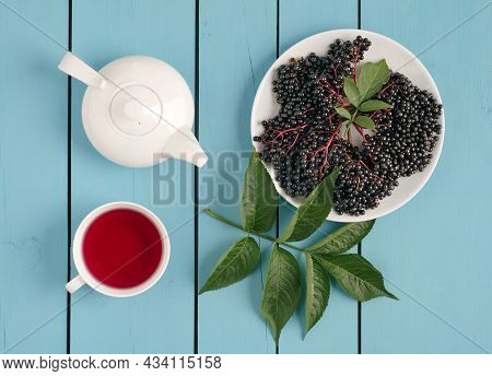 Bunch Of Elderberry Berries With Green Leaves, Drink In Cup And Teapot On Wooden Light Blue Backgrou