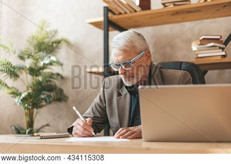 Paper Work. An Adult Businessman Fills Out A Tax Form In The Office At The Table. Bureaucratic Forma