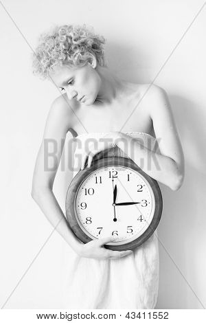 Young scrawny woman with big clock in hands, black and white photo.