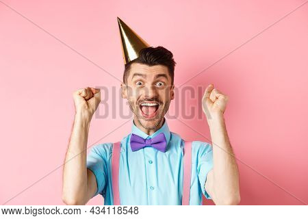 Holidays And Celebration Concept. Cheerful Young Man Celebrating Birthday Party In Cone Hat And Bow-