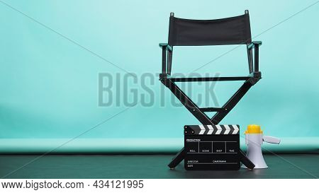 Black Director Chair With Megaphone And Clapperboard Or Movie Clapper Board On Green Or Tiffany Blue