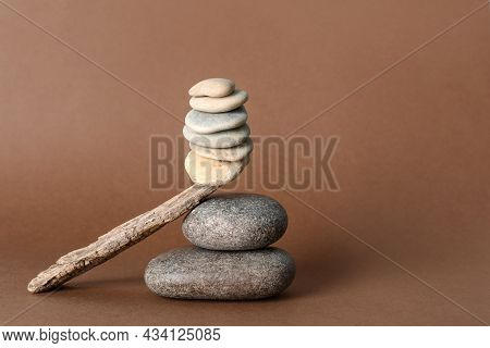 Stack Of Stones Balancing On Wooden Stick Against Brown Background, Space For Text. Harmony Concept