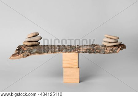 Stacks Of Stones Balancing On Wooden Stick Against Light Background. Harmony Concept