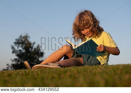 Child Boy Reading Book, Laying On Grass In Field On Sky Background. Portrait Of Clever Kids. Kids Su