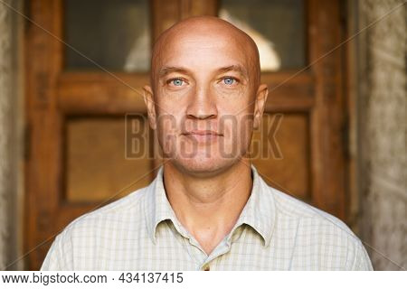 Portrait Of Bald Man Against The Backdrop Of Building Close-up. Model Over 40, Blue Eyes And A Light