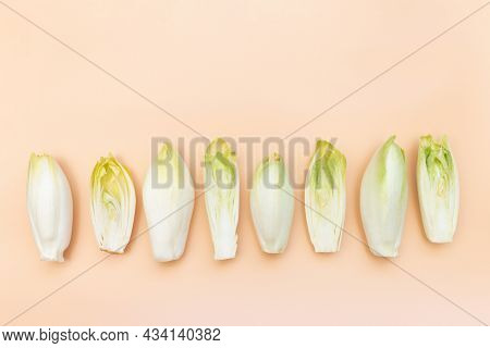 Many Raw Endives Salad Roots Or Chicory On Light Orange Background, Flat Lay, Healthy Organic Meal C