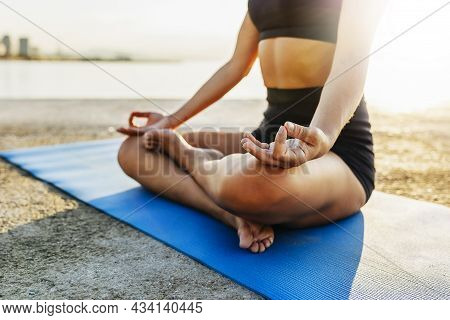 Woman Doing Yoga By The Sea At Sunrise - Sporty Young Woman Meditating In Lotus Position On The Beac