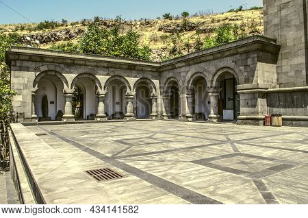 A Basalt Arched Gallery With A Courtyard Laid With A Pattern Of Light Gray Basalt Next To The Buildi