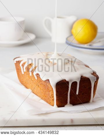 Lemon Cake With Poppy Seeds Pouring With White Icing. Home Made Sweet Morning Breakfast On Baking Pa