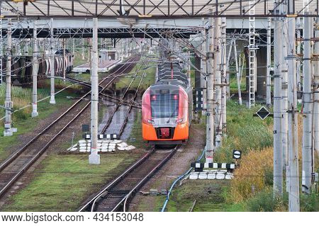 Top View Of Modern Russian Intercity High Speed Train Under The Bridge. Industrial Landscape With Pa