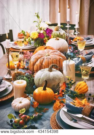 Thanksgiving celebration traditional dinner setting food concept. Festive decoraded table with pumpkins, vegetables, flowers and candles