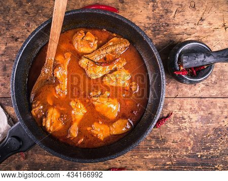 Chicken Stewed With Paprika, Tomatoes In A Pan With A Wooden Spoon On A Wooden Table, Top View