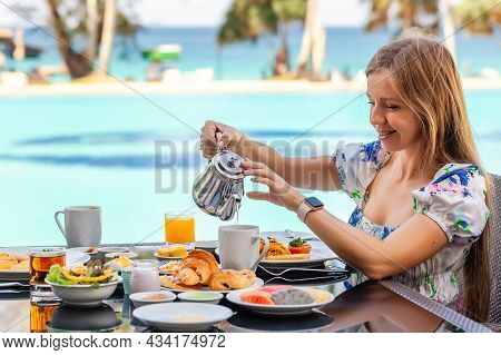 Smiling Woman On American Breakfast Pooring Next To Poolside In Resort. Morning Food Near Swimming P