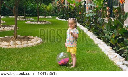 Cheerful Cute Little Girl, 3 Years Old, With Two Ponytails On Her Head, Wearing A Multi-colored T-sh