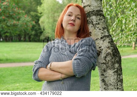 Attractive Young Woman With Red Hair In A Blue Knitted Sweater Stands By A Birch Tree And Looking At