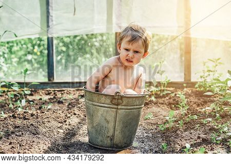 Positive Little Boy Sits Uncomfortably In Old Metal Bucket Of Warm Water On Kitchen Garden Bed In Ol
