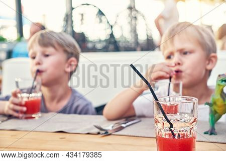 Cute Little Blond Brothers Drink Fresh Strawberry Juice With Straws Sitting At Wooden Table In Cafe