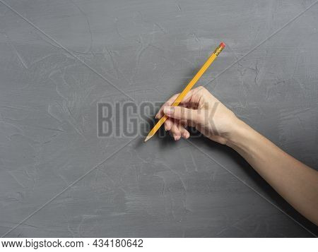 A Woman's Hand Holds A Pencil On A Gray Textured Background. Horizontal Photo, Copy Space.