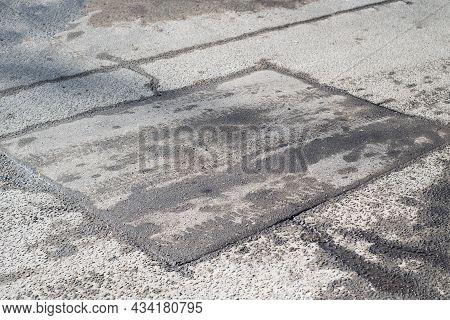 Patch On The Asphalt. Repair Of An Asphalt Road. Old Cracked Asphalt