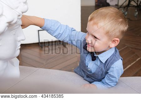 Portrait Of A Five-year-old Boy In Profile. Boy Touches A Plaster Bust While Lying On The Couch. Boy
