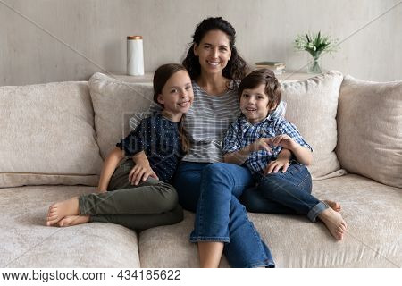 Portrait Of Happy Caring Young Mother Cuddling Adorable Kids.