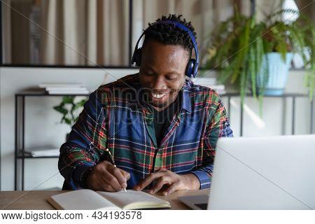 Happy Student Guy In Wireless Earphones Taking Distance Learning Course