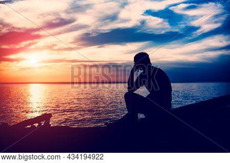 Toned Photo Of Sad And Lonely Young Man Silhouette At Seaside In The Evening