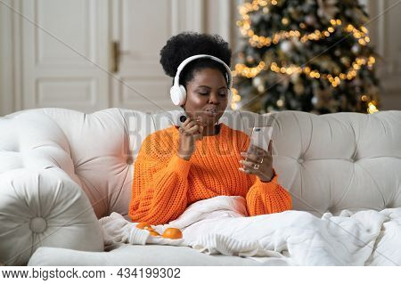 Relaxed Black Woman Spend Christmas Holiday At Home Sitting Under Blanket In Living Room With Decora