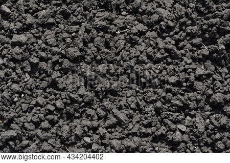 Asphalt Or Bitumen Raw Materials For Road Construction. Gray Asphalt Texture. A Whole Dry Roadbed.