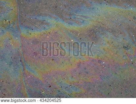 Layer Of Gasoline On A Surface Of Wet Asphalt As A Sign Of Environmental Contamination - A Rainbow W