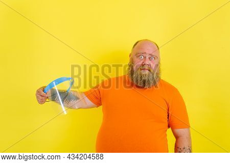 Doubter Man With Beard And Tattoos Is Worried About A Protective Face Shield Against Covid-19