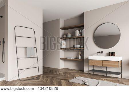 Corner Of The Beige Shower Room Interior With An On Trend Round Mirror Over A Modern Vanity, A Niche