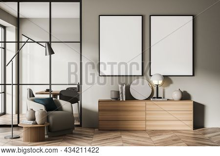 Two Canvases On The Beige Wall Of The Living Room Interior With A Sideboard And An Armchair. A Dinin