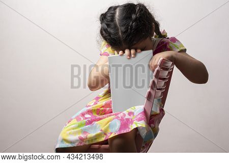 Shy Little Girl Hiding Her Head Behind A Story Book With Blank Cover In Front Of Her Body, Editable